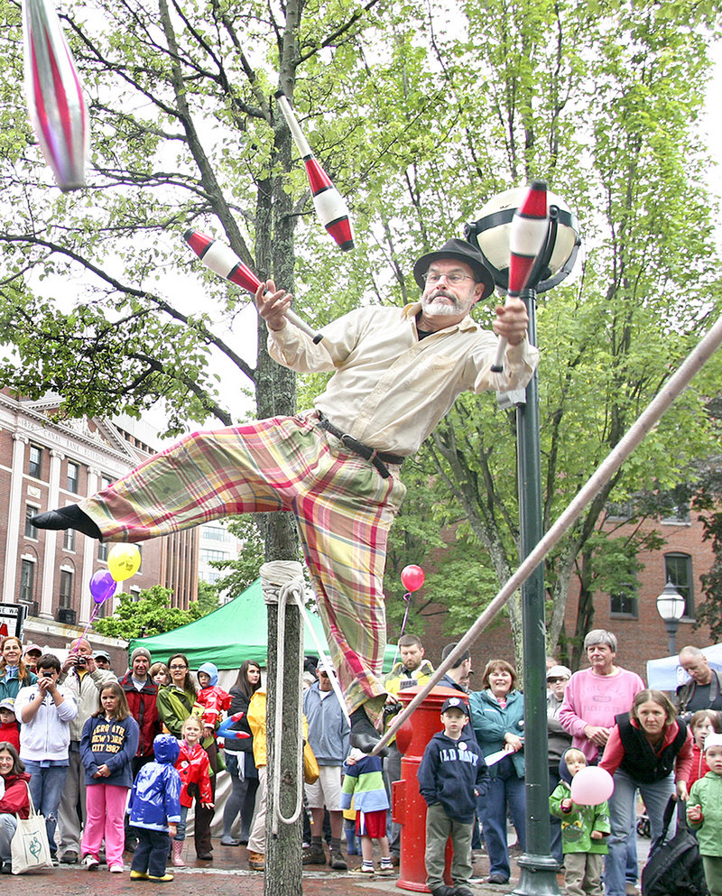 George Weatherbee of Portland balances on a slack rope while juggling in Tommy's Park during Old Port Festival.