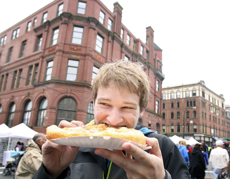 Casey Olesen of Portland eats fried dough Sunday at during the 38th annual Old Port Festival in Portland, which drew an estimated 25,000 people.