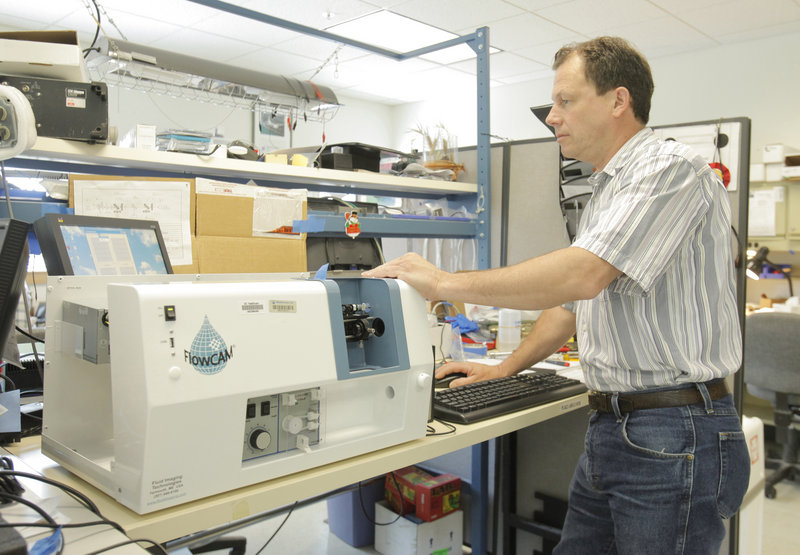 Ilmars Labrencis, an electronics technician at Fluid Imaging Technologies in Yarmouth, upgrades a customer's FlowCAM unit, which takes images of particles in liquids at microscopic levels. Fluid Imaging is expanding from oceanographic research into municipal water testing and industrial uses.