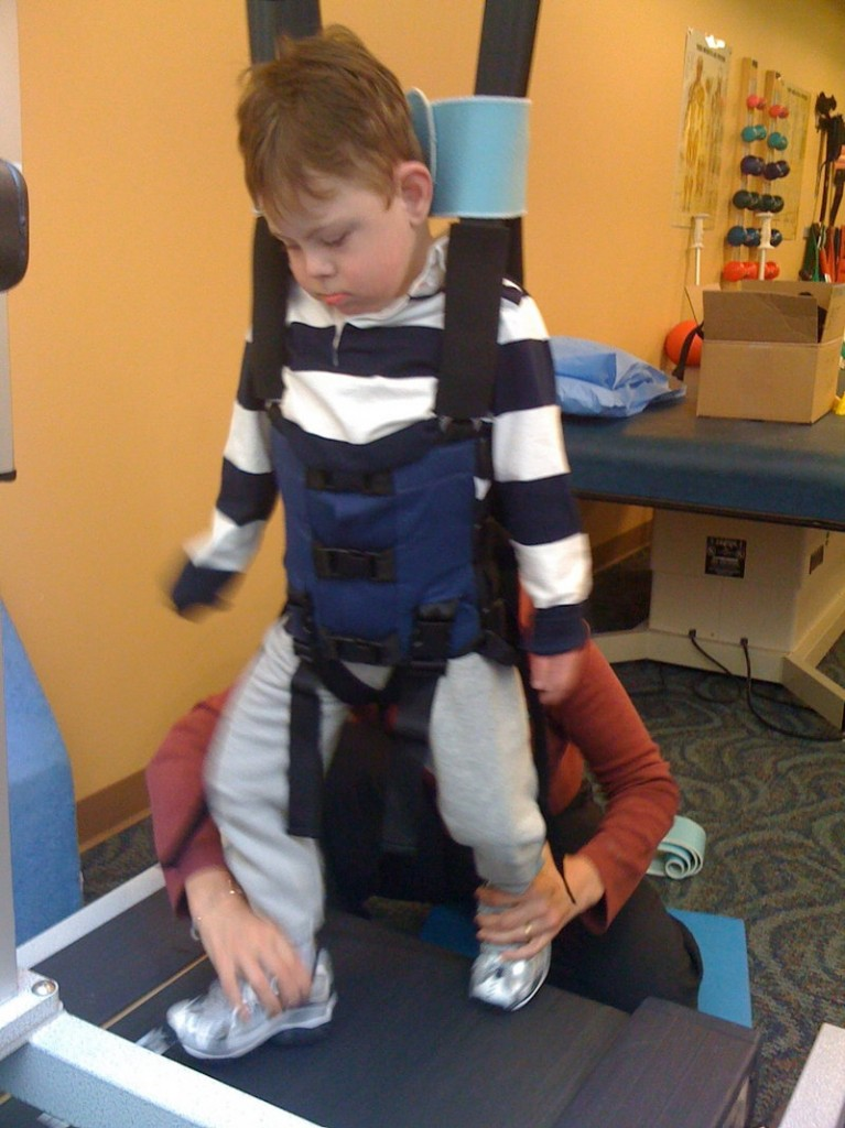 Miles Chumsae, a 6-year-old at the Morrison Center in Scarborough, tests a LiteGait trainer during therapy.
