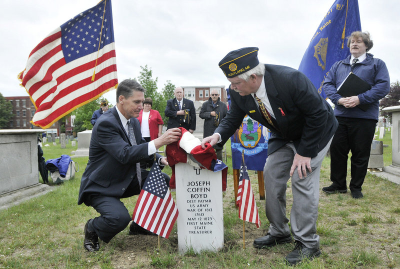 Former state Treasurer David LeMoine, left, and the commander of American Legion Post 17, Curtis Ballantine, unveil the headstone for Joseph Coffin Boyd on Tuesday in Eastern Cemetery. At right is Herb Adams, the historian who worked to obtain the grave marker.