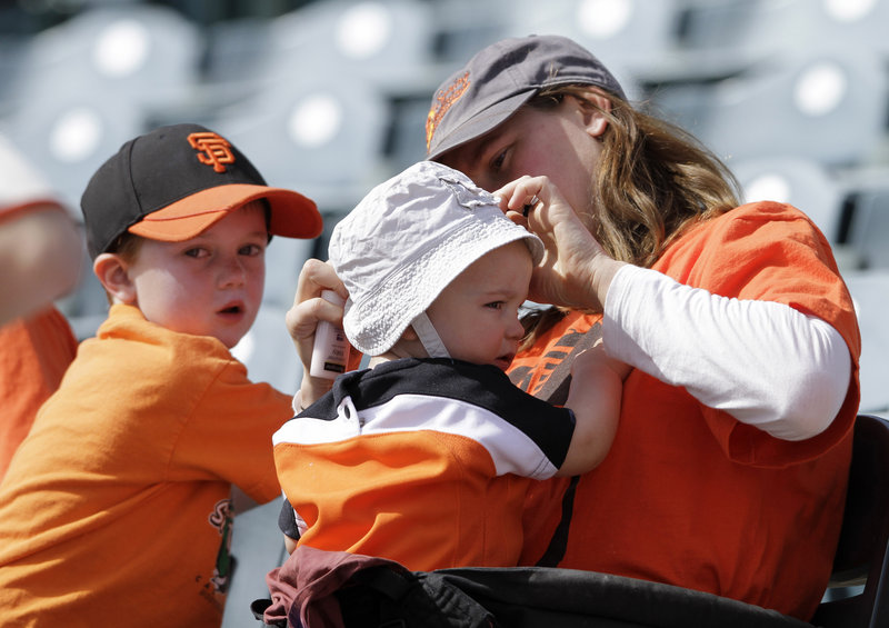 Erica Fortescue, right, of San Francisco applies sunscreen on her 11-month-old daughter Nico during an Oakland Athletics baseball game. At left is Nico's brother Theo, 4.