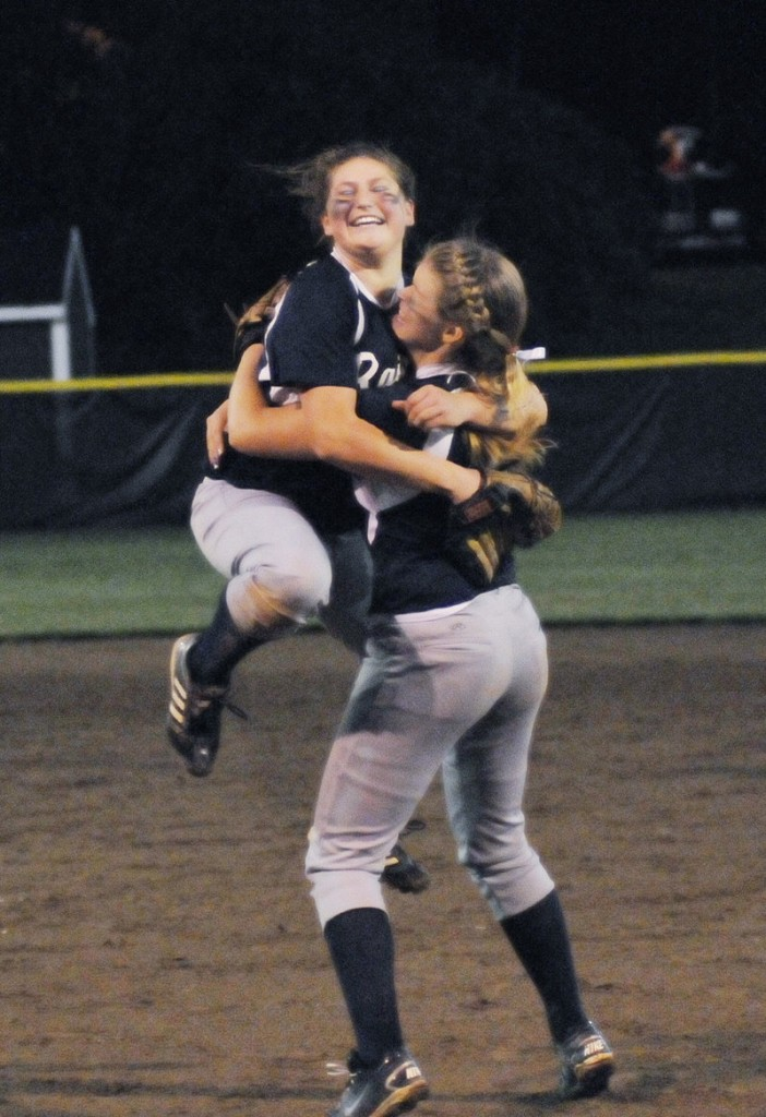Fryeburg Academy pitcher Sarah Harriman jumps into the arms of first baseman Ashley Watkins after the 6-1 victory against Oak Hill.
