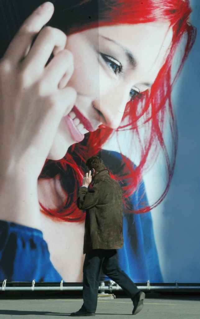 """A cellphone user passes a giant poster at the CeBIT computer fair in Hanover, Germany. """"The operative word is 'possibility,'"""" said one cancer expert, who points out that there's little evidence linking cancer with cellphone use."""