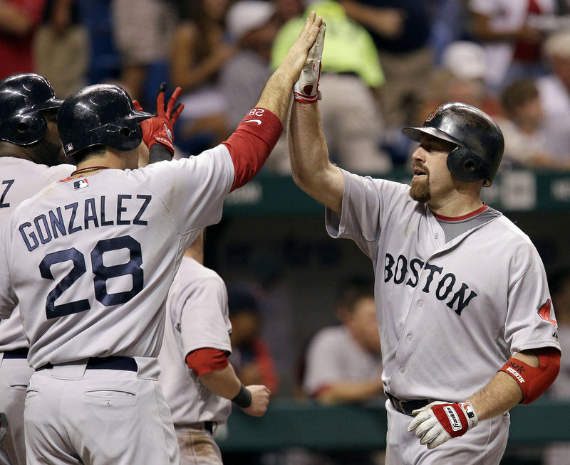 Kevin Youkilis of the Boston Red Sox, right, is welcomed by Adrian Gonzalez after hitting a three-run homer in the seventh inning of a 3-0 victory Wednesday night against Tampa Bay.