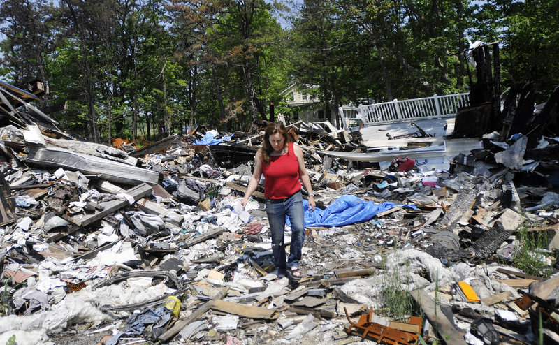 Marcia Lee walks through the rubble of her family's home at 2 Piney Woods Road in Saco, which burned in February. Lee, who is out of work, and her daughter had just moved in there with her mother, who had lapsed on her homeowner's insurance and is behind on her taxes.