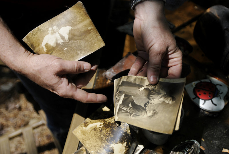 Marcia Lee flips through family photos found in the rubble where her family's home once stood. The city has offered to dispose of the rubble but would charge the house's owner – Doris Loomer, Lee's mother – which would result in a lien on the property.