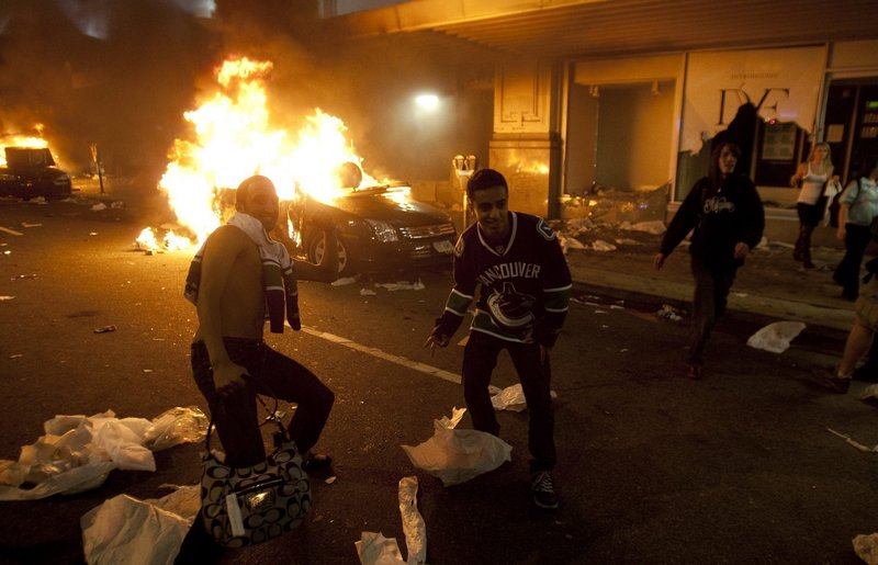 Men in Vancouver Canucks hockey jerseys are seen in downtown Vancouver, British Columbia, on Wednesday. It's estimated more than 50 businesses were damaged and 15 cars were burned, including two police cruisers.