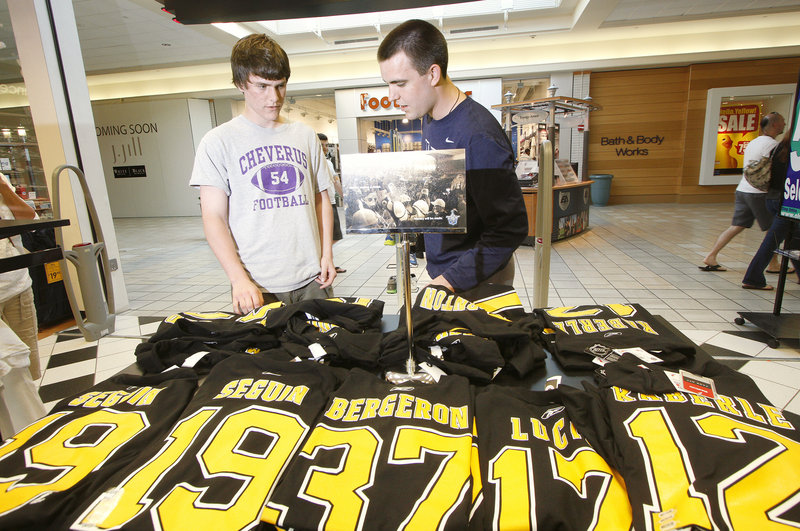 """Andrew MacGillivray, left, and his brother Doug shop for Boston Bruins jerseys at Olympia Sports at the Maine Mall in South Portland on Thursday. Merchants there said """"Bruins stuff has been flying out the door"""" as hockey fans responded to the team's Stanley Cup victory."""