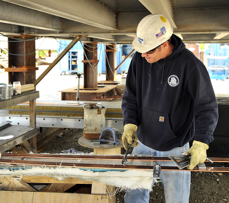 Mark Seavey, a master electrician for Cianbro, assembles a solid copper ground bar system under one of the modules.