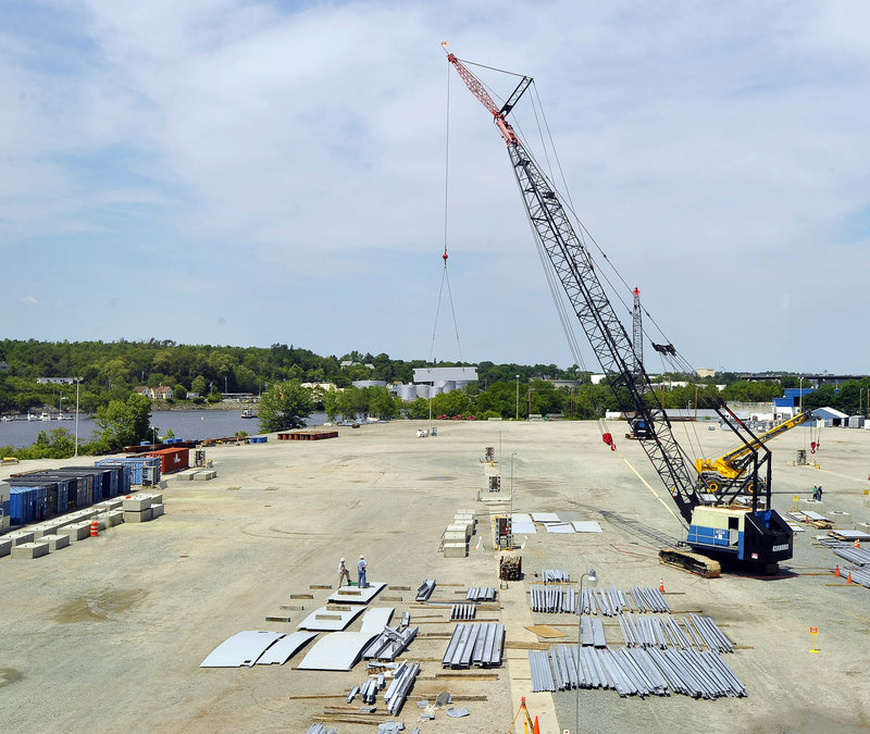 Workers use a large crane to lay out the pieces that will be assembled into 22 modules being built for Vale, a mining company, at the Cianbro site in Brewer.