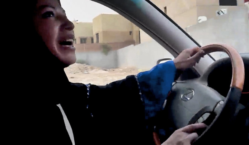 A Saudi Arabian woman drives a car Friday in Riyadh in a campaign to defy the monarchy's male-only driving rules. About 40 women took part. No arrests were reported, but one woman was ticketed for driving without a license.