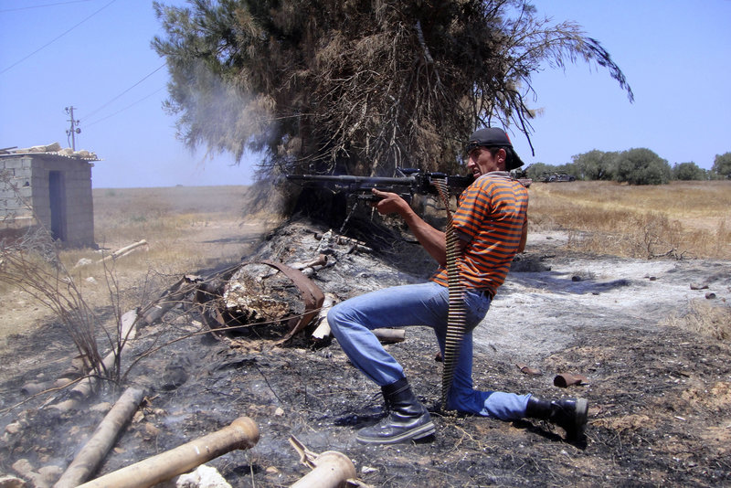 A rebel fighter fires a machine gun toward pro-Gadhafi forces Friday at the front line of Dafniya in Misrata, Libya.