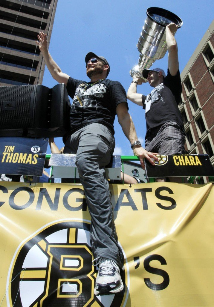 Tim Thomas, still sporting his playoff beard, waves to the crowd as Zdeno Chara holds the Stanley Cup during Saturday's parade celebrating the Bruins' championship.