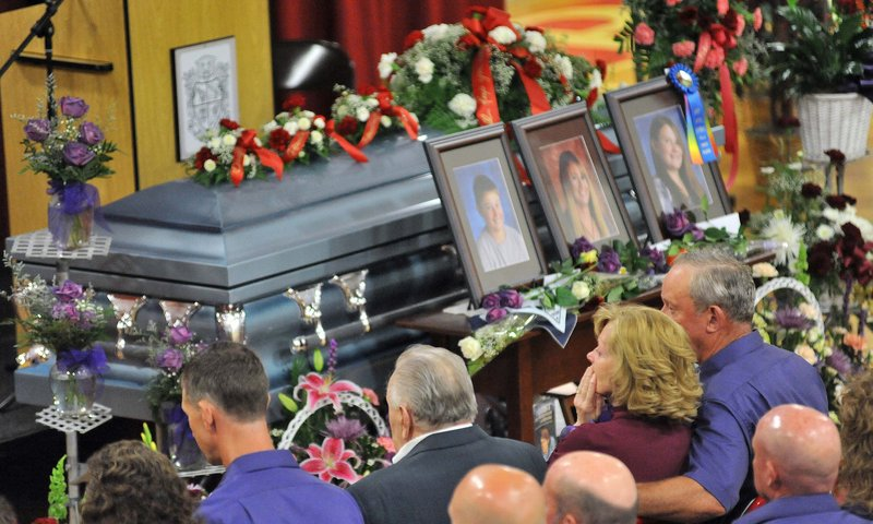Ralph Bagley, right, holds his wife, Linda, as they sit in front of the casket that holds the bodies of their daughter and two grandchildren, who were killed last week.