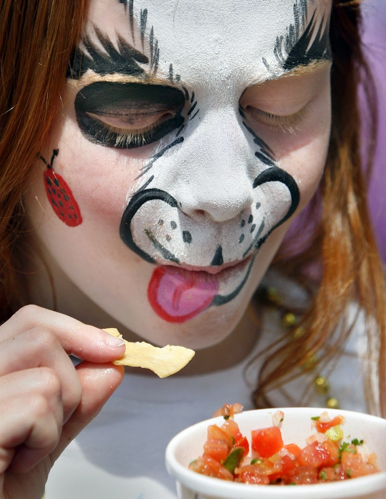 Nichole Roberts, 8, of Kittery got her face painted like a puppy, then enjoyed a snack of chips and salsa.