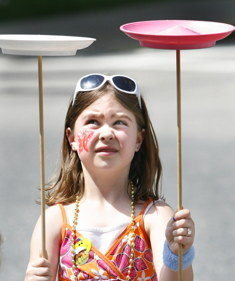Emma Webb, 7, of Kittery spins plates at the party. It was her first time spinning plates, she said, and she found it to be fairly easy.