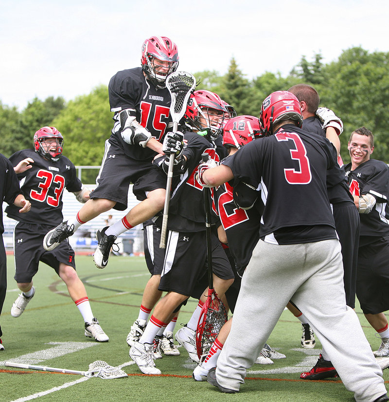 The Scarborough boys' lacrosse team prepares for Dalton Finley, left, to land on the celebratory pile after the team secured the Class A state championship Saturday with a 6-4 win over Lewiston.