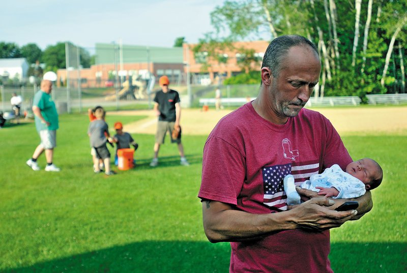 Donn Chamberlain holds his infant son, Rain, while son Bailey, 9, practices with his team in Norridgewock.