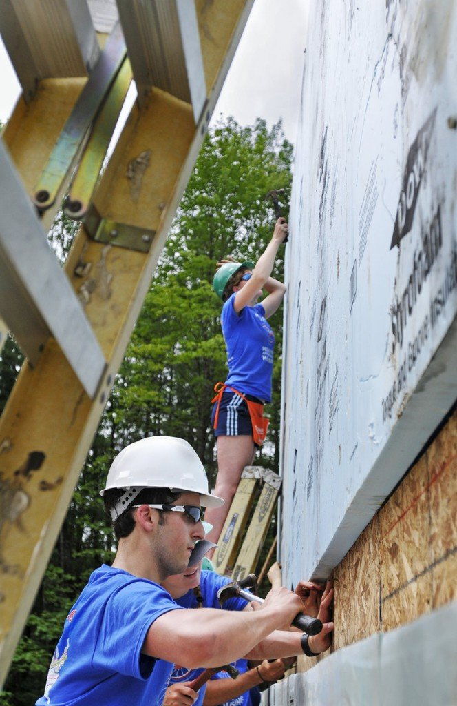 Bike & Build members Aaron Miller of Bala Cynwyd, Pa., front to back, Becky Carman of Green, Ohio, and Kate Weigel of Bangor work on a house Monday on South Street in Freeport for Habitat for Humanity.