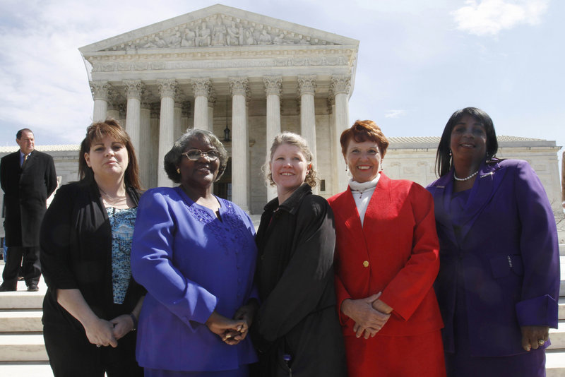 The five plaintiffs in the sex-discrimination lawsuit against Walmart, from left, Stephanie Odle of Norman, Okla., Betty Dukes of Pittsburg, Calif., Deborah Gunter of Palm Springs, Calif., Christine Kwapnoski of Bay Point, Calif., and Edith Arena of Duarte, Calif., pose for a photo outside the Supreme Court. The nine justices on the Supreme Court all agreed in Monday's ruling that the case could not proceed as a class action.