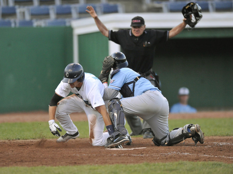 Tom Verdi of the Raging Tide gets the safe call after beating the tag by Laconia Muskrat catcher Dylan Kelly and scoring on a double by Matt Marquis in the sixth inning of a game Tuesday night at Old Orchard Beach.