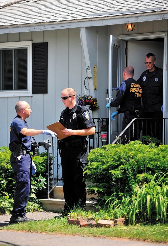 Investigators with the Maine State Police Evidence Response Team and a Farmington police officer stand outside the apartment where an elderly woman was attacked early Tuesday.