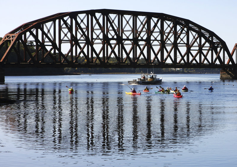 Kayakers on a 2008 Pemaquid Paddlers outing explore the Sheepscot River in Wiscasset as a lobster boat checks traps.