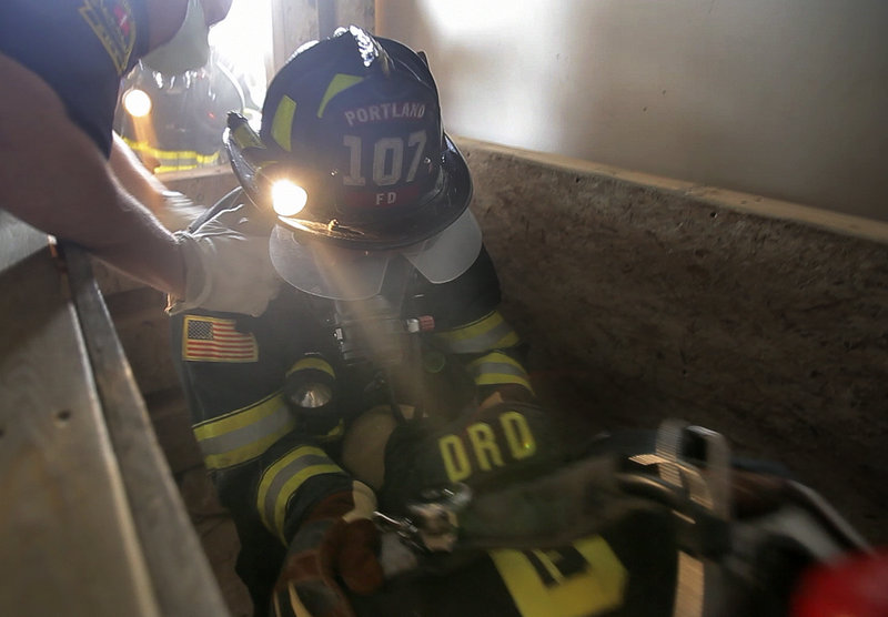 Portland firefighter Roger Robinson tries to lift a downed firefighter up from a confined space during firefighter training at the International Marine Terminal in Portland on Wednesday. Sessions include a number of simulated life-threatening situations.