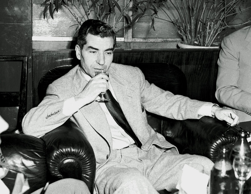 """Reputed mobster Charles """"Lucky"""" Luciano, seen in 1946, sips a drink during a news conference in the Excelsior Hotel in Rome. A 3-inch thick official U.S. government file with information about more than 800 Mafia figures has surfaced and will be auctioned by Bonhams New York."""