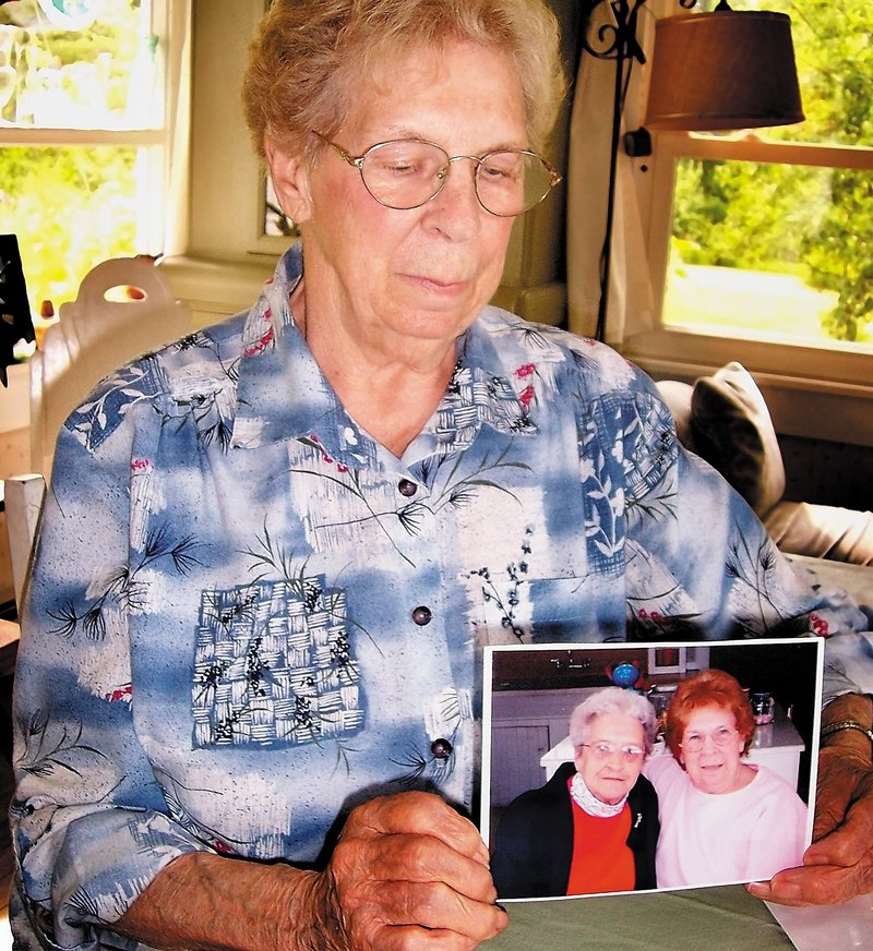 Lois Seamon, 81, sits at her kitchen table with a photo of herself and lifelong friend Grace Burton, 81, who died after being attacked in her Farmington apartment early Tuesday.