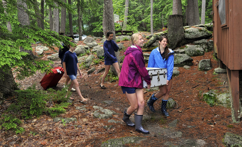 Camp counselors Laura Douglas, left, and Rebecca Lounsbury help move campers' belongings into cabins Thursday on opening day for Camp Wohelo in Raymond, a haven along the shore of Sebago Lake.