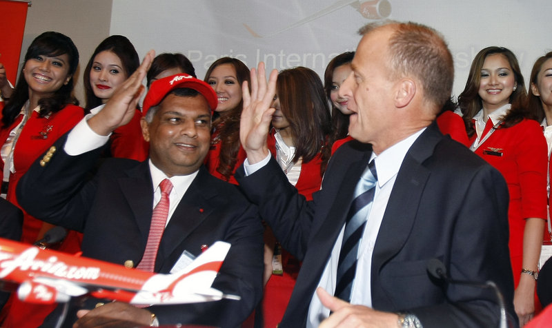Airbus chief executive officer Tom Enders, right, and AirAsia chief executive officer Tony Fernandes high-five after the signing of an agreement for the sale of 200 Airbus A320neo jetliners during the Paris Air Show on Thursday.
