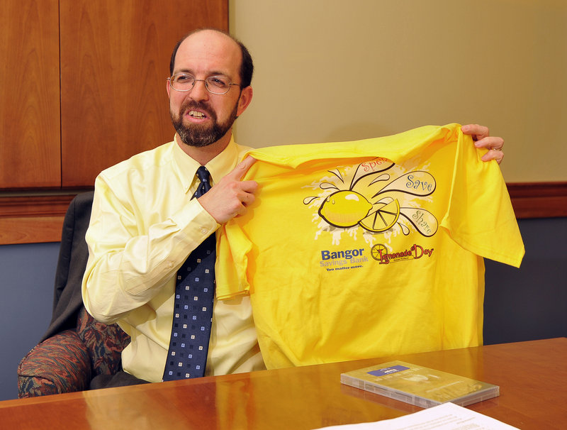 Yellow Light Breen, executive vice president of Bangor Savings Bank, holds up a T-shirt from one of the bank's community projects.