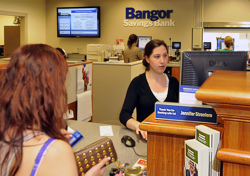 Jennifer Straniero, a teller at the Hammond Street branch of Bangor Savings Bank, serves a customer. On the wall behind her, a flat-screen monitor announces news of supported events in the community.