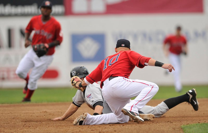 Sea Dogs shortstop Ryan Khoury tags out Brian Dozier of the Rock Cats trying to steal second base during the first game of a doubleheader Tuesday night at Hadlock Field.