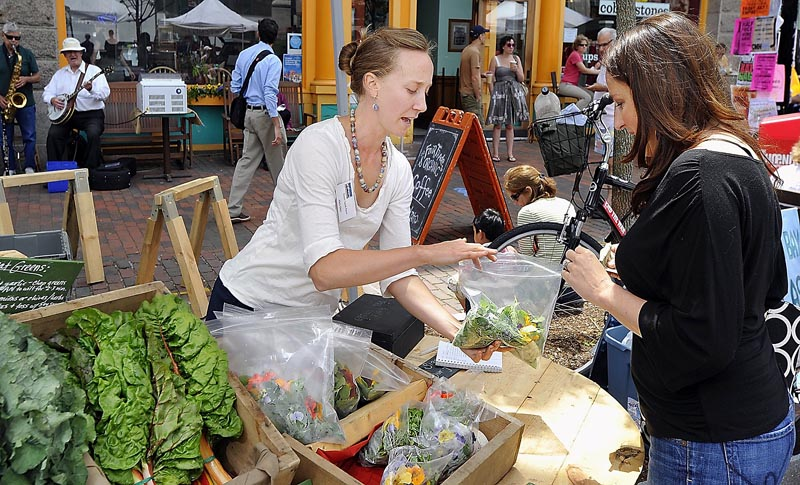 Stephanie Hedlund, owner of Clara Burke Kitchen, shops for local produce at the Monument Square Farmers Market. Here she buys fresh greens and edible flowers from Mary Ellen Chad of Green Spark Farm.