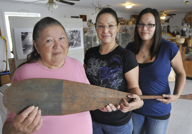 Descendants of famous Passamaquoddy chief Tomah Joseph, from left, Joan Dana, Natalie Dana and Cassandra Dana show off a paddle made by Joseph and on display at the Passamaquoddy Cultural Heritage Center & Museum in Indian Township.