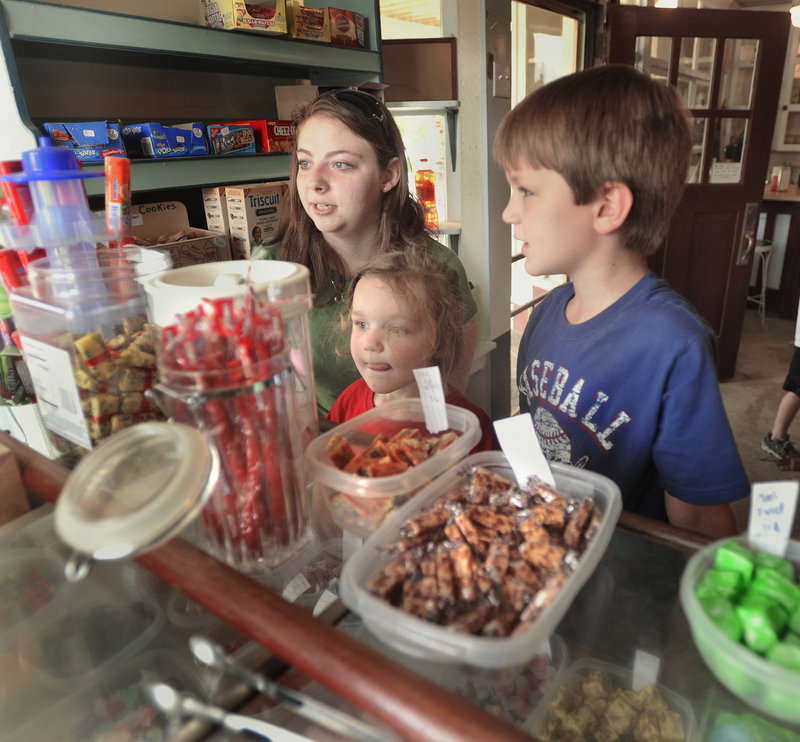 Breonna Hatch helps Saco children Hannah Clarke, 3, and Isaiah Clarke, 7, choose from the candy on display at the Way Way Store.