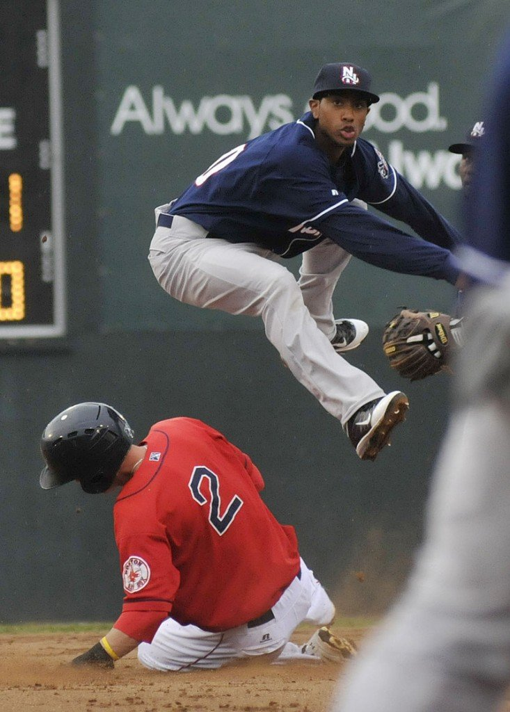 Jeremy Hazelbaker of the Portland Sea Dogs slides hard Sunday night but fails to stop Justin Jackson of the New Hampshire Fisher Cats from getting the throw to first base for a double play.