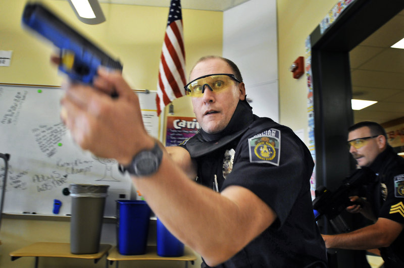 Gorham Police Officer Mike Brown clears a room at the Westbrook Middle School Tuesday, during live-fire training. Officers faced mock hostage situations and fired paintballs for ammunition.
