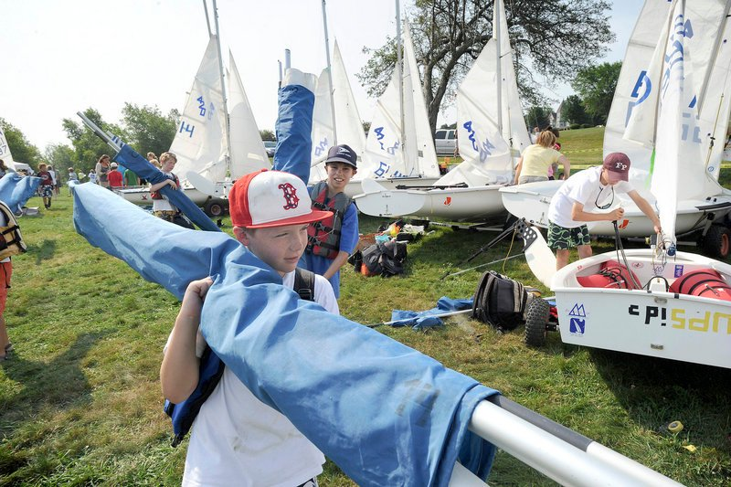 Ten-year-old Connor Reilly of Medfield, Mass., works to assemble his Optimist sailboat. The regatta gives new racers a taste of competition and is also a great venue for older racers, said Sarah Helming, director of programs at SailMaine.