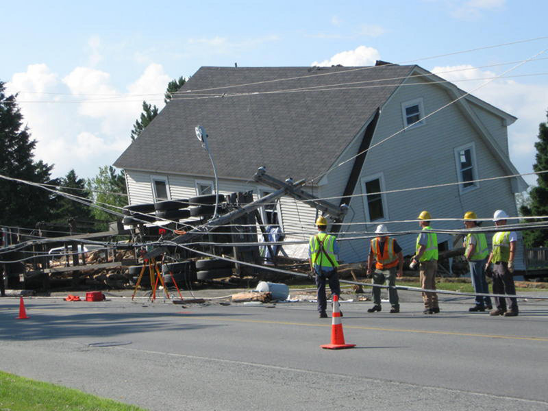 A logging truck rests on its side along Route 201 in Jackman, next to the home damaged by the logs that rolled off the truck's bed. Authorities said the truck was driving through Jackman near the Canadian border around 2:30 a.m. when it struck telephone poles and rolled on its side, spilling its cargo. A 5-year-old boy sleeping inside the house was killed.