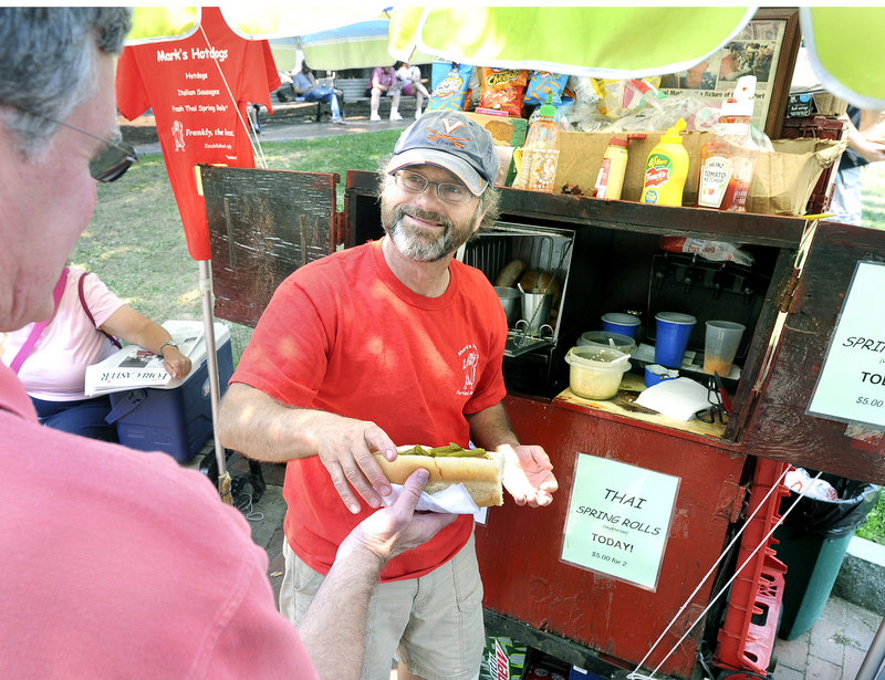Mark Gatti sells hot dogs and sausages at Tommy's Park in Portland on Wednesday. Gatti bought his first food cart at 23, but his three-year plan is now going on 28 years.