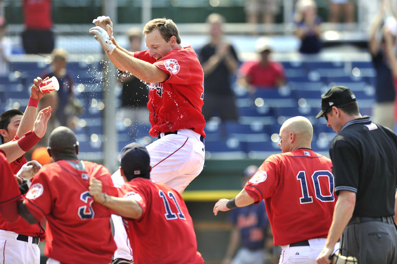 Mitch Dening is welcomed by his Portland Sea Dogs teammates Wednesday after hitting the first walk-off homer of his Double-A career, producing a 10-9 victory against the Binghamton Mets at Hadlock Field.
