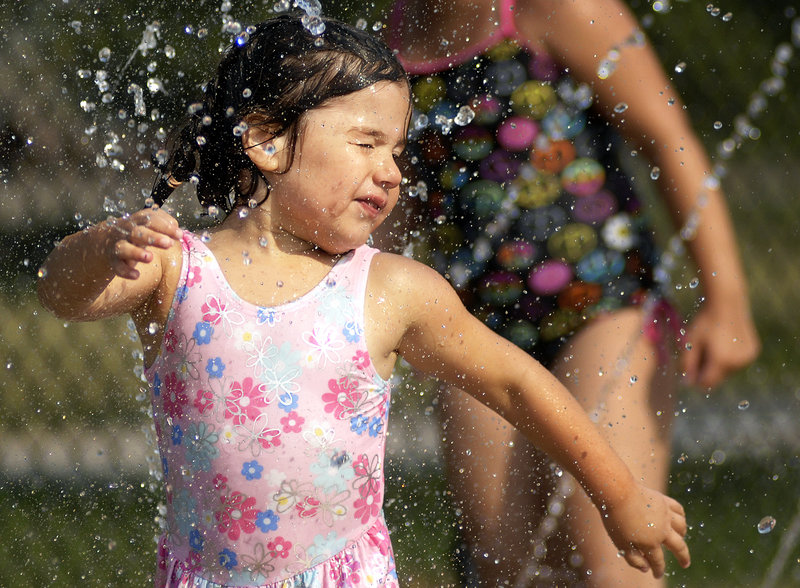 Sofia Andrade, 3, of South Portland cools off in the splash pad at the Kiwanis community swimming pool in Portland on Wednesday. The weather forecast suggests the pool will have plenty of visitors in the next few days.