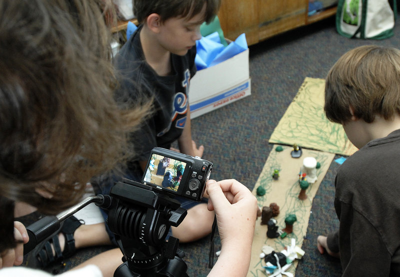 Declan Porter, 10, of South Portland operates the camera Wednesday while Ryan Wallace, 12, of Cape Elizabeth, center, and Ian Madden, 11, of Falmouth maneuver the clay figures.