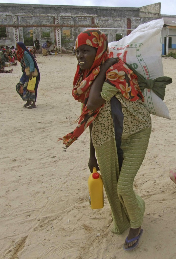 A women leaves a camp for displaced people in Mogadishu, Somalia, after receiving emergency food rations Wednesday.