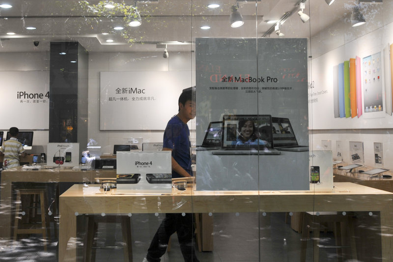"A man dressed as an Apple store employee looks out from a window of a shop masquerading as a bona fide Apple store in downtown Kunming, in southwest China's Yunnan province, Thursday. A store visitor said ""some things were just not right."""