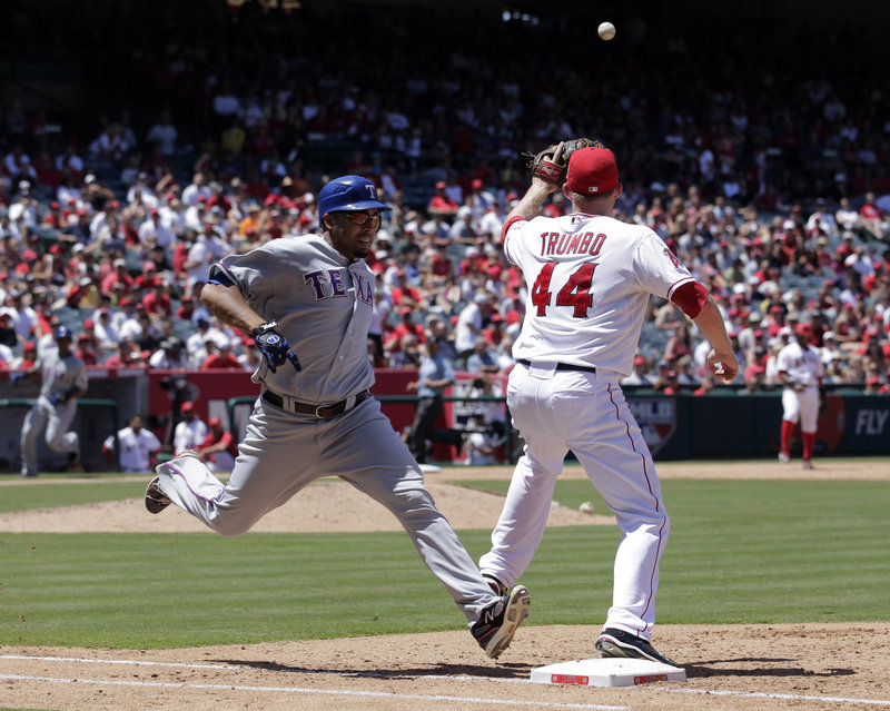 Nelson Cruz of the Texas Rangers beats out an infield single Thursday as Mark Trumbo of the Los Angeles Angels awaits the throw during the sixth inning. The Angels won, 1-0.
